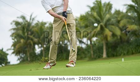 Unrecognizable Asian Golfer Swinging Club Hitting Ball In Golf Course