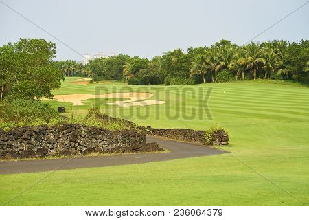Fairway & Bunkers In Beautiful Tropical Golf Course Surrounded By Trees