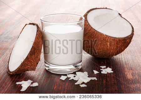 Healthy Coconut Milk In Glass With Shredded Coconut With Coconut Flakes On Wooden Table.