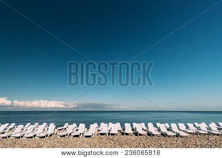 Beach Sun Loungers By The Sea. Chaise-longues, Chaise Longue On Beach In Sunny Day. Sunbeds In Row