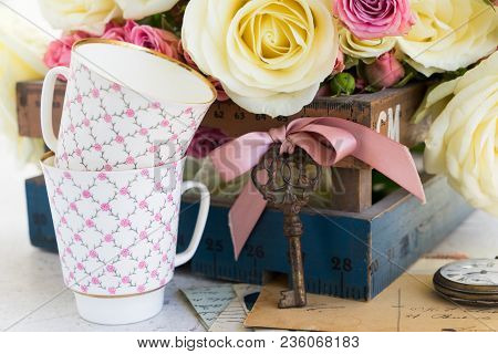 Pink And White Blooming Roses With Two Cofee Cups And Antique Key