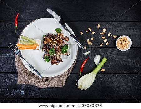 Barbecue Ribs With Vegetables And Sauce, Served On The White Plate With Cutlery And Linen Napkin, On