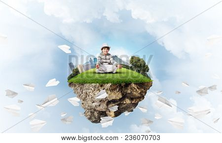 Young Little Boy Keeping Eyes Closed And Looking Concentrated While Meditating On Flying Island Amon