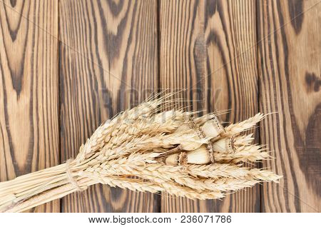 One Bundle Of Wheat And Poppy Tied Up Of Brown Rope On Old Rustic Wooden Planks