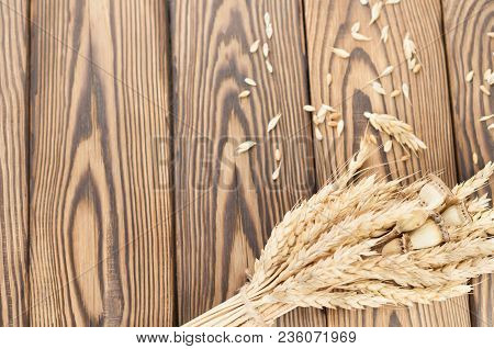One Bundle Of Wheat And Poppy Tied Up Of Brown Rope And Lot Of Scattered Grain On Old Rustic Wooden