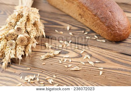 One Bundle Of Wheat And Poppy And Lot Of Scattered Grain And Single Whole Bread On Old Rustic Wooden