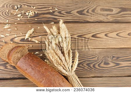 One Bundle Of Wheat And Poppy And Lot Of Scattered Grain And Half Of Bread With Slices Of Bread On O