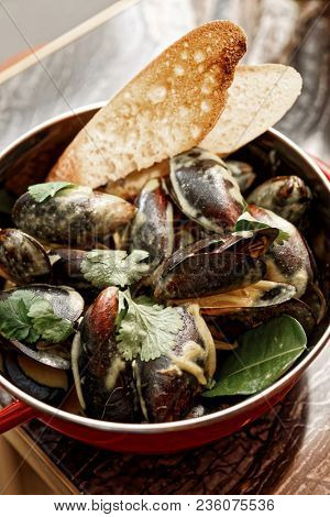 Mussels cooked with curry and served in metal pot, Asian style food, toned picture