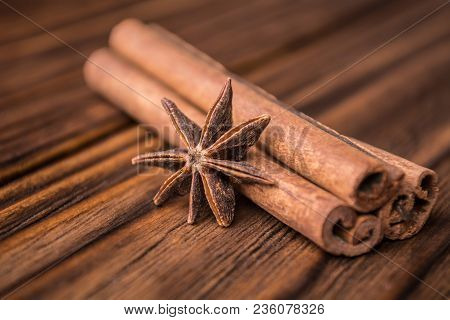 Dried Anise Star And Cinnamon Sticks On A Wooden Background. Ingredients For Tea Or Mulled Wine.