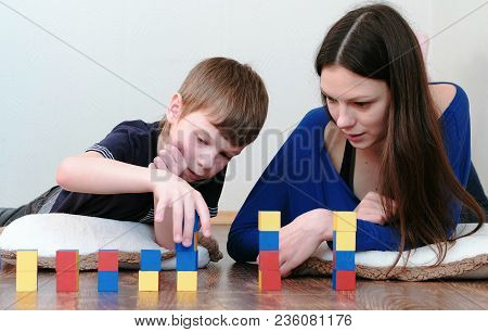Building A Towers From Blocks And Cubes. Mom And Son Playing Together With Wooden Colored Education