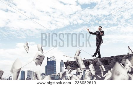 Businessman Walking Blindfolded Among Flying Documents On Concrete Bridge With Huge Gap As Symbol Of