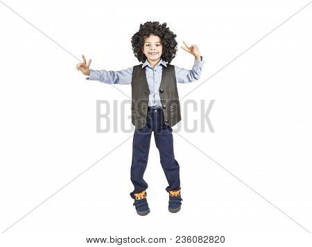 A Little Boy In A Funny Afr Wig Makes A Victory Gesture, Isolated On White