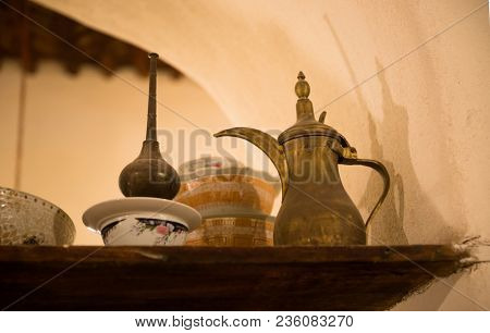 Antique arabic utensils- Antique Arabic Dallah and other traditional utensils are displayed on the shelf.