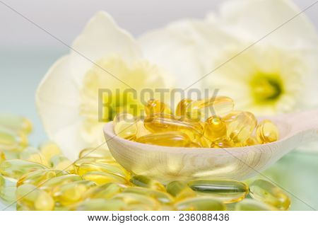 Fish Oil Capsules In Wooden Spoon With Flower Background. Fish Oil Dietary Supplement. Pharmaceutica
