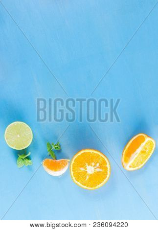 Citrus Slices Close Up On Blue Background - Assorted Citrus Fruits With Mint Leaves