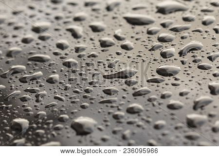 Drops Of Rain Or Water Drop On The Hood Of The Car. Rain Drops On The Surface Of The Car Or On The I