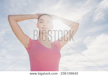 Confident Stylish Young Girl In Sports Clothes Trains Outdoors In The Sun, Gaining Strength