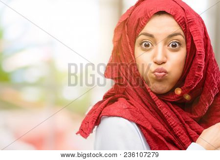 Young arab woman wearing hijab puffing out cheeks, having fun making funny face