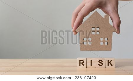 Property Investment And House Mortgage Financial. Risk Management Concept. Hand Putting Wooden Home