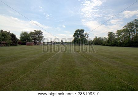 Vast Open Mowed Field Of Green Grass With Trees In The Background In Summer Under A Blue Sky