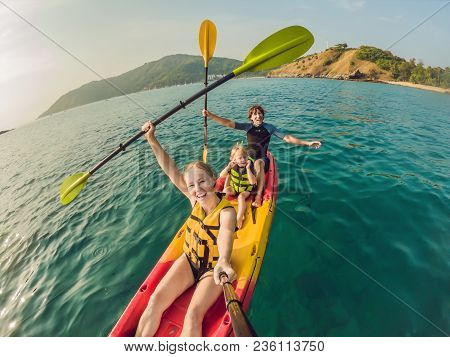 Happy Family With Kid Kayaking At Tropical Ocean.