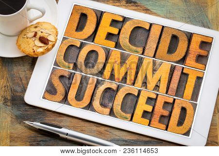 Decide, commit, succeed word abstract in vintage letterpress wood type on a digital tablet with a cup of coffee