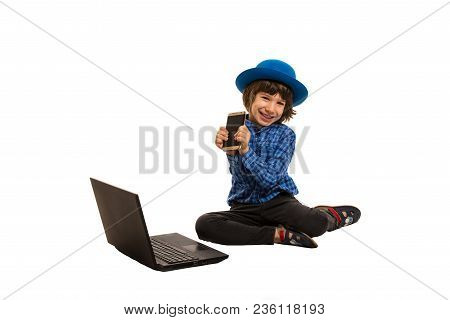 Cheerful Elegant Boy Showing Smart Phone And Sitting Down Near Laptop Isolated On White Background