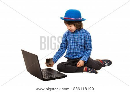 Small Elegant Boy With Laptop And Smart Phone Sitting Down Isolated On White Background