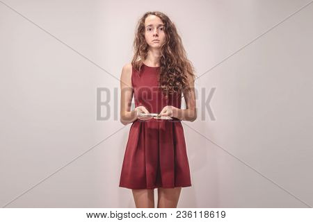 Pretty Young Girl In Red Dress Needs More Money On A Gray Background.