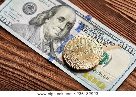 Golden Bitcoin And Dollars On Wooden Background. A Symbolic Coins Of Bitcoin On Banknotes Of One Hun