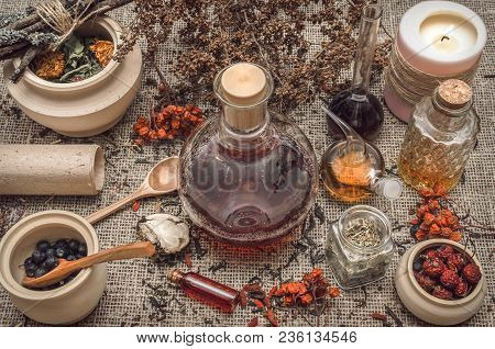 Herbal Medicine Concept. Alternative Medicine. Dry Curative Herbs And Wild Berry Essential Oil And O