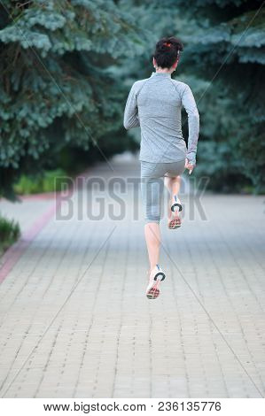 Runner Legs At Back View In A City Park. Rear View Sport Woman Running.