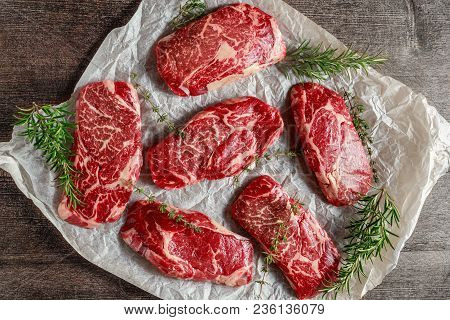 Raw Organic Marbled Beef Steaks With Rosemary And Thyme On Cooking Paper.