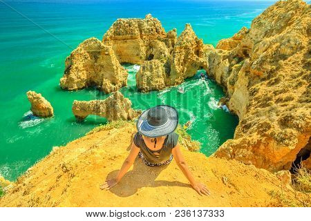 Tourism In Algarve. Summer Holidays In Portugal, Europe. Lifestyle Tourist Sitting On Promontory Of