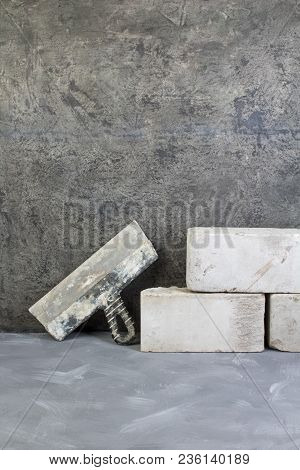 Bricks, Putty Knife On The Gray Concrete Background. Copy Space. Top View