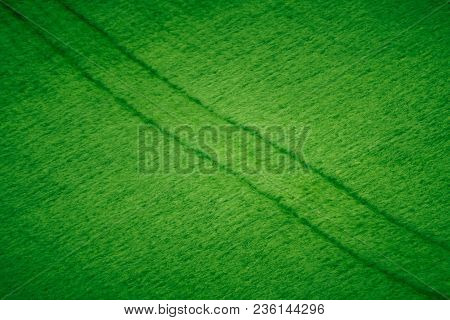 Abstract Background Texture Of Tractor Tracks Through Lush Green Crops