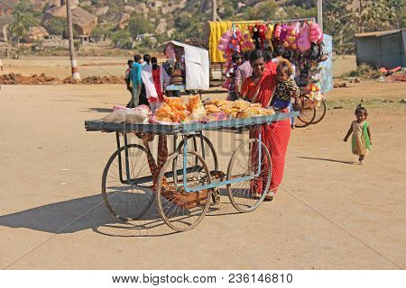 India, Hampi, 02 February 2018. Street Shopping On A Cart. A Girl In A Sari Sells Sweets And Snacks.