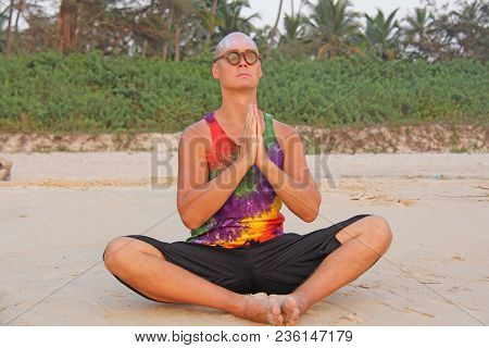 Bald Man Freak In Bright Clothes And Round Glasses At A Freak Parade, Festival, On The Beach. India,