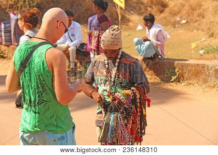 India, Goa, January 24, 2018. Street Trading. Bald Tourist European Buys Beads Or Jewelry From An In