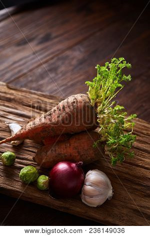 Bundle Of Carrots With Soil Over Rustic Wooden Background, Side View, Close-up, Selective Focus, Low