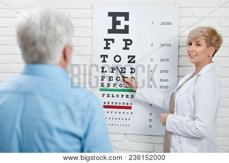 Backview Of Expirienced Oculist Checking Patient's Vision.