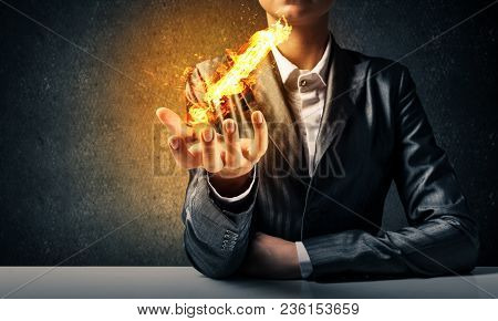 Cropped Image Of Businessman In Suit Presenting Flaming Exclamation Mark In His Hand With Dark Wall