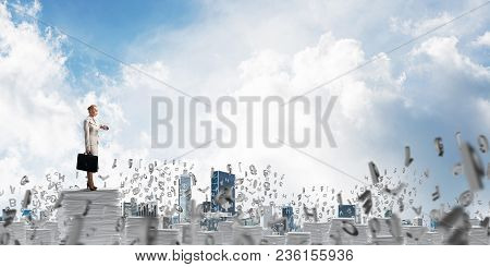 Confident Business Woman In Suit Standing Among Flying Letters With Cloudly Skyscape On Background.