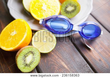 Healthy Breakfast, Sport, Fitness, Diet Concept. Citrus Fruit On A White Plate And A Swimming Mask O