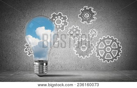 Lightbulb With Cloudly Skyscape Inside Placed Against Sketched Gear Mechanism On Grey Wall On Backgr