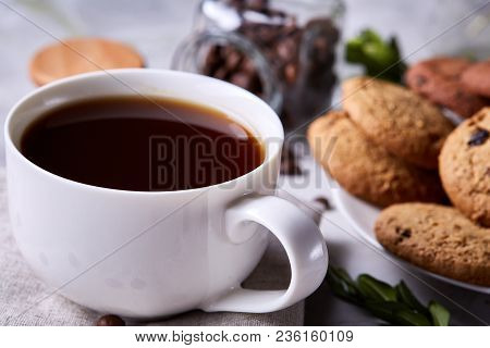 Morning Coffee In White Porcelain Cup, Crispy Chocolate Chips Cookies On Homespun Napkin Over Wooden