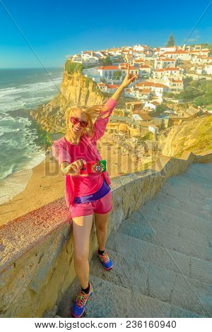 Happy Sporty Woman Takes Selfie Of Azenhas Do Mar On Atlantic Ocean. Tourist Takes Pictures By Mobil