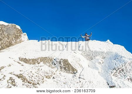 Happy The Mountaineer Climbed The Mountain Top Covered With Ice And Snow, Man Hiker Celebrating Succ