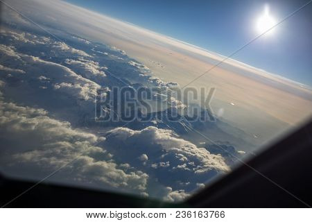 View from a cockpit of a commercial airliner airplane over a beautiful mountain range