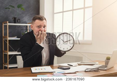 Confused Businessman In Suit Holding Clock And Looking At It. Portrait Of Man With Watches At Office